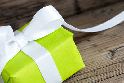 Green Present with White Ribbon, Closeup on Wood